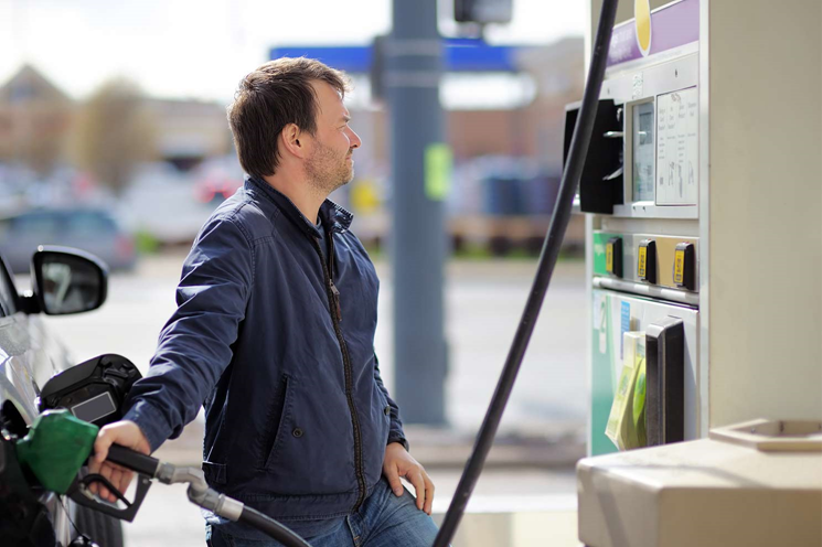 A delivery driver fills up his car with fuel
